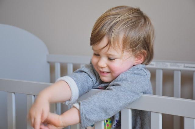 un bébé devant ses barreaux de lit