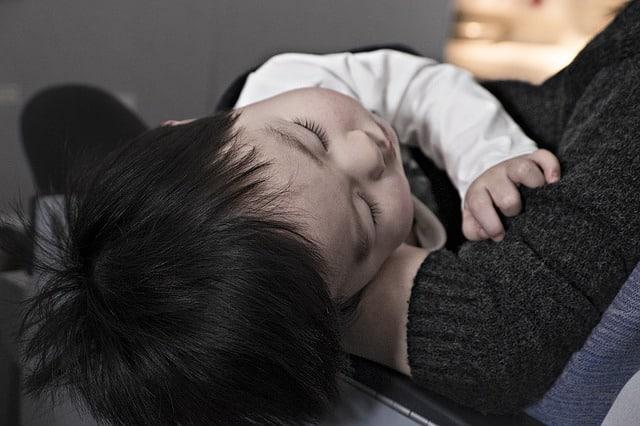un enfant malade dans les bras de sa maman