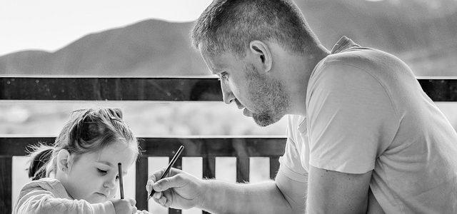 une enfant qui écrit avec son pere